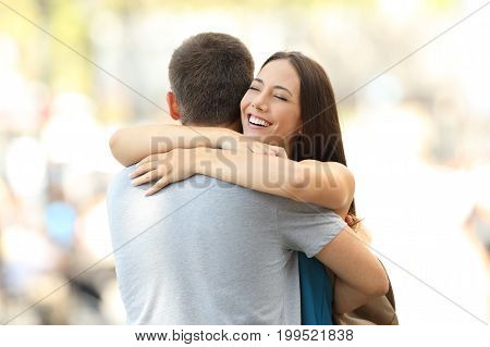 Happy girlfriend hugging her partner after encounter on the street