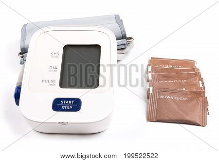 Brown sugar and blood pressure monitor isolated on a white background