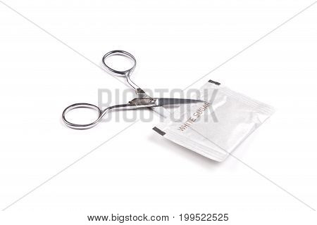 Scissor cutting white sugar packaging isolated on a white background. Concept of cutting down sugar intake.