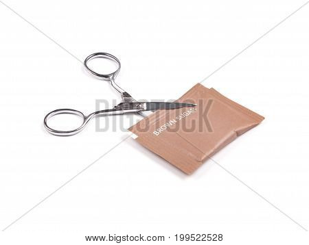 Scissor cutting brown sugar packaging isolated on a white background. Concept of cutting down sugar intake.