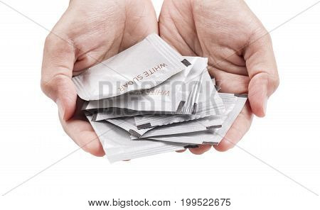 Hand filled with white sugar packs. Isolated on white background.