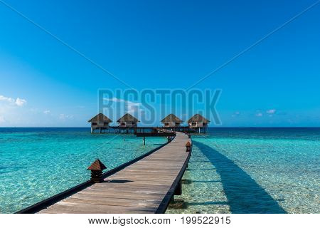 MAAFUSHI MALDIVES - MARCH 01 2016: Wide angle picture of wooden way to go to the bungalows on top of turquoise water in a island close to Maafushi in Maldives