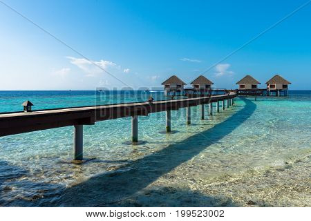 Horizontal picture of wooden way to go to the bungalows on top of turquoise water in a island close to Maafushi in Maldives
