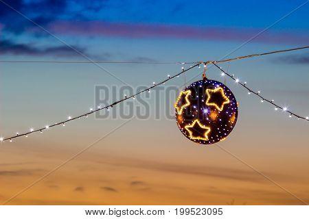 Modern Suspended christmas street lights at sunset