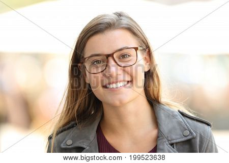 Front view portrait of a beautiful satisfied girl wearing eyeglasses on the street