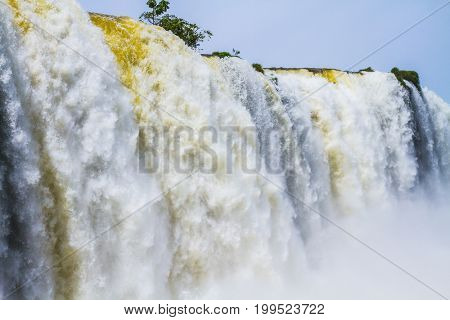 Rumbling world of falling water. Iguazu Falls in South America, on the border of three countries. Concept of active and extreme tourism