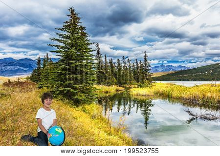 The concept of ecological and active tourism. Handsome boy with a globe in his hands laughs cheerfully in delight from clouds forect  and lake. Magnificent landscape in the Rocky Mountains