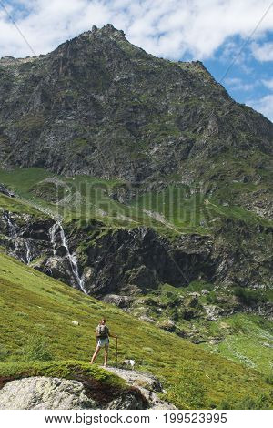 Beauty young woman travel with backpack and dog jack russel in mountain