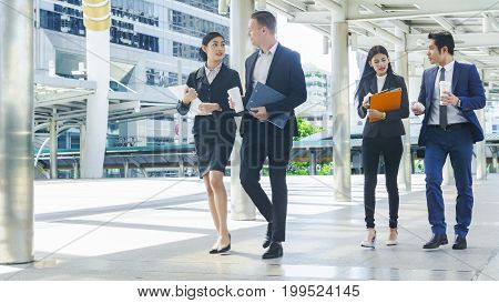 team of business people smart man and woman walk in rush hour at outdoor pedestrian walk way and talk together with breakfast food and coffee on the hand in good feeling with the city space building