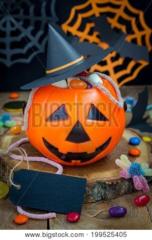 Halloween Jack o Lantern bucket overflowing with candy vertical copy space