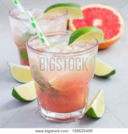 Cold pink cocktail with fresh grapefruit lime and ice cubes on concrete background paloma square format