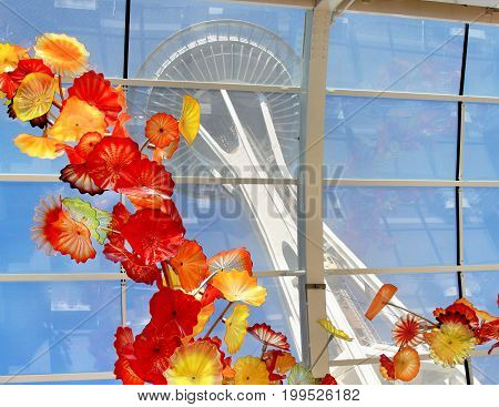 SEATTLE July 29 2017: Chihuly Garden and Glass museum featuring one of Dale Chihuly's largest sculptures suspended from the ceiling of the glasshouse. Space Needle is seeing in the background.