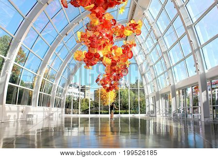 SEATTLE July 29 2017: Chihuly Garden and Glass museum featuring one of Dale Chihuly's largest sculptures suspended from the ceiling of the glasshouse. City buildings are seen in the background.