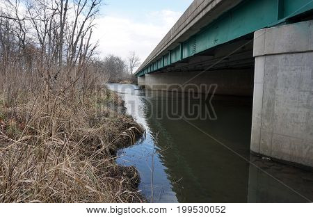 SHOREWOOD, ILLINOIS / UNITED STATES - DECEMBER 6, 2015: The Du Page River flows under the Jefferson Street Bridge near the Hammel Woods Forest Preserve.