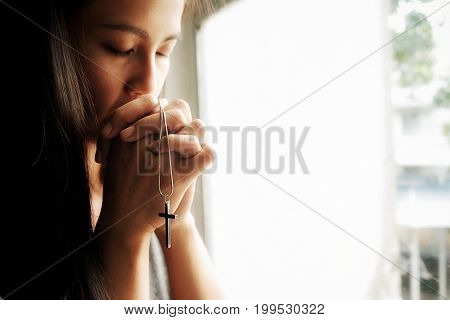 Beautiful calm girl with closed eyes praying on holy bible.