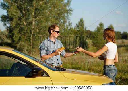 Couple in love. Road adventure. The girl gives the boyfriend the keys of the ignition. They are standing by the car.