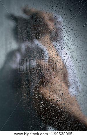 Beautiful woman posing wearing shirt posing in shower behind glass