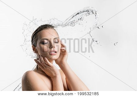 Beautiful woman her eyes shut enjoyng water stream and splashes from the side