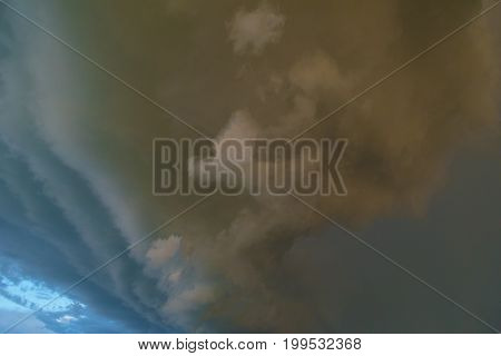 Impending storm with dark clouds on clear blue sky. Illustration of danger.