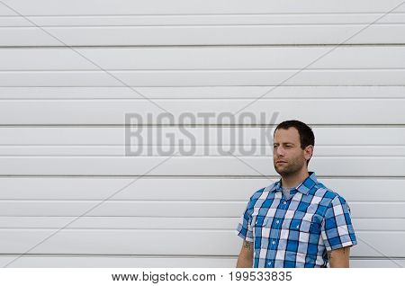 Man in a plaid shirt looking to the left alone against a white background.