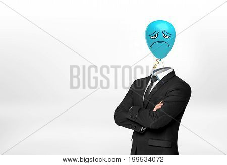 A businessman on white background stands with crossed hands and a blue sad face balloon instead of his head. Work attitude. Negative thoughts. Pessimistic leader.