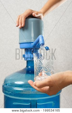 closeup of hands pouring water from bottle with a pump