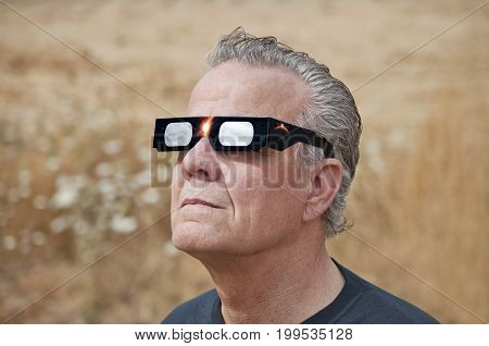 Man viewing solar eclipse with solar glasses in country field