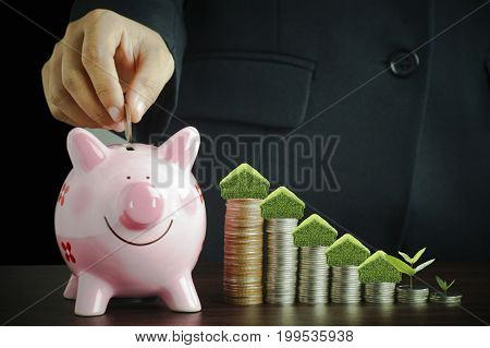 business people put coin in piggy bank and stacked of money coins growing up concept in business about loan sellingfinance and buying home house