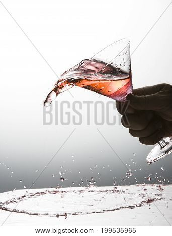 Cocktail being spilled out of a martini glass