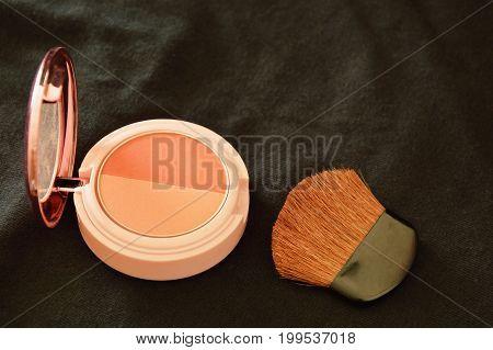 blusher powder cartridges and brush on black fabric background