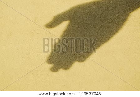 shadow of human hand on old cement wall