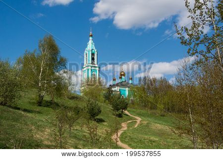 Canonic view of small russian ortodox church over the hill beautiful summer landscape with trees and a path Moscow Russia.