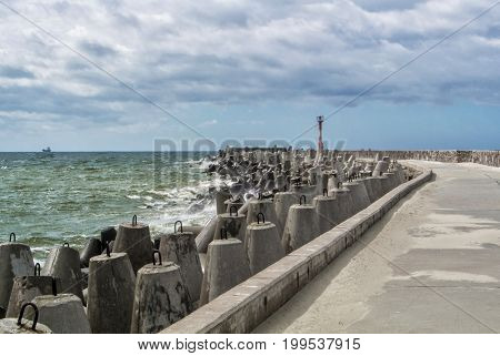 An embankment of Baltic sea at the city Baltiysk on cloudy summer day a view to a pier with a little lighthouse and a mole the most western point of Russia Kaliningrad region.