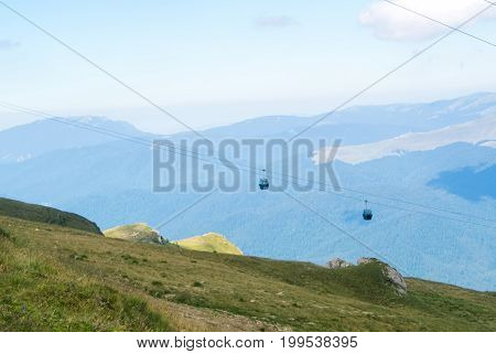 Panoramic View Over The Carpatian Mountains And Two Cableway Cabins Moving To The Top Of The Mountai
