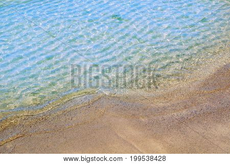 A background close up macro view of beautiful transparent clear soft sea wave at the beach Baltic coast near St. Petersburg Russia. A symbol of summer holidays.