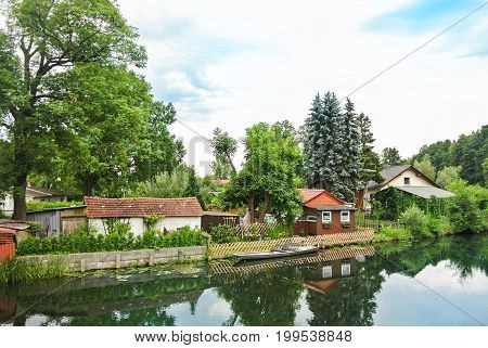 A Wooden House Between Big Old Trees At The Canal Embankment, Blue Pines And A Canoe Near The Wooden