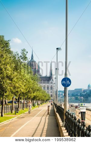 BUDAPEST HUNGARY - JULY 24 2016: Bike path at the Danube embankment at the center of Budapest and signs and Parliament building at the background Hungary.