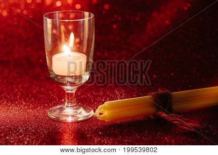 Golden Light Of Candles Burning In Wine Glass With Light Effect And Red Blurred Bokeh Background
