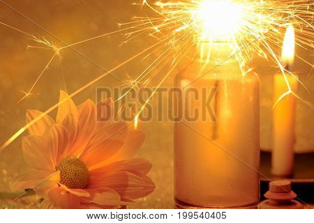 Concept Of Sparklers In Glass Jar At Night And Fresh Yellow Flower With Blurred Golden Light Candle
