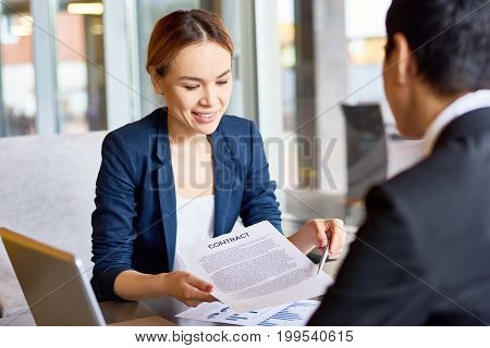 Portrait of attractive Asian entrepreneur discussing cooperation conditions with her business partner while having meeting in spacious restaurant, she holding contract in hands