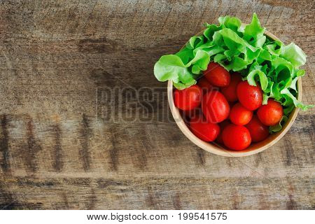 Fresh tomato and lettuce in wood bowl put on wood table. Top view or flat lay of tomato and green oak lettuce with copy space for background. Fresh green oak lettuce and tomato prepare for cooking. Green lettuce and red tomato concept.