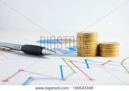 Stack of coins on a financial chart