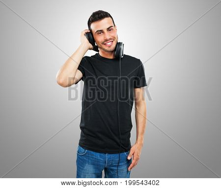 Young mann listening to music through his headphones