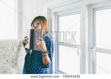 Beautiful hipster woman Charming girl with stylish glasses stand side of window and holding red book in living room concept of lifestyle and education.