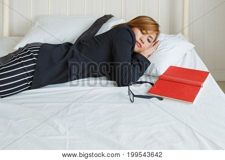 Business woman sleep at bed and reading red book in her room Charming girl in uniform and glasses concept of self-learning for business.
