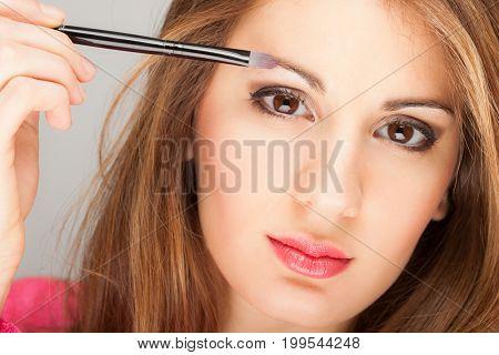 Portrait of a beautiful woman applying eye shadow