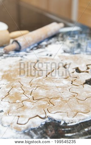 Cutting holiday gingerbread cookies out of dough