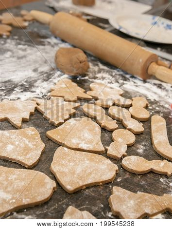 Making holiday gingerbread cookies with dough and roller