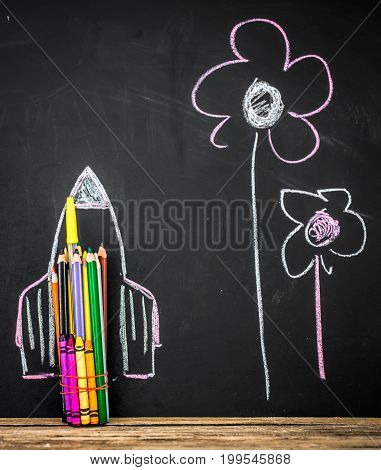 back to school rocket made out of pencils on a black background, concept of education