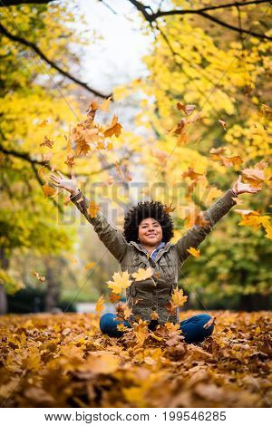 Girl playfully throwing up fallen autumn leaves over her head